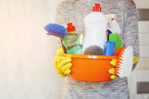 Woman hands holding tub with supplies for house cleaning.