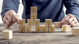 Front view of a man arranging wooden blocks with hand drawn yellow lightbulb in a random structure. Conceptual of research, education and innovation.